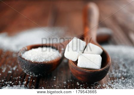 White sand and lump sugar in spoons on wooden background