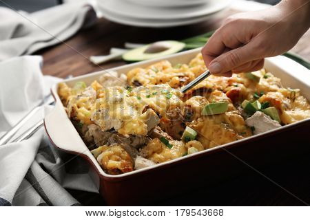 Woman taking portion of roasted chicken with cheese from casserole dish