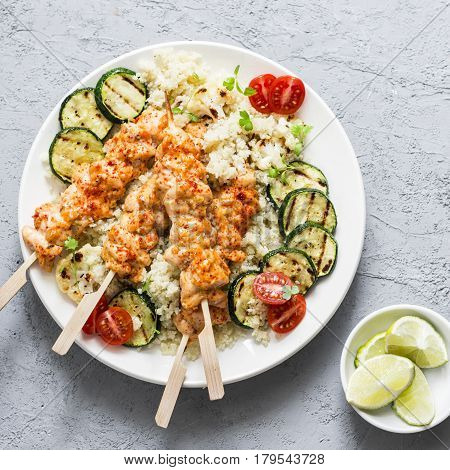 Chicken kebab cauliflower cous cous and grilled zucchini. Mediterranean style healthy eating on a gray background top view