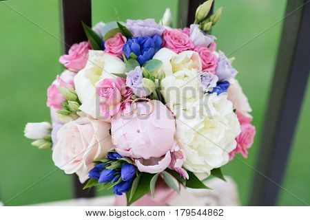 Bride bouquet of roses and peonies and wedding rings