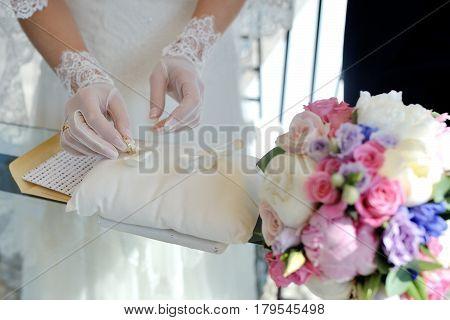 Bride hand take wedding rings during wedding ceremony