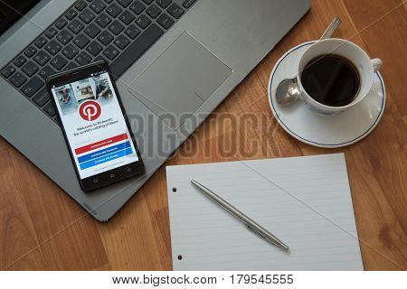 Nitra, Slovakia, march 28, 2017: Pinterest application in a mobile phone screen. Workplace with a laptop, an earphones, notepad, pen and coffee on wooden background