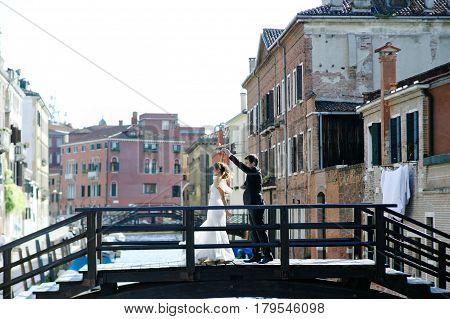 Bride and groom dancing over a bridge in wedding day in Venice Italy
