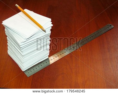 A large Pile of square white sheets ruler and pencil lies on a brown table. The photo of the stack of paper can be used as a background