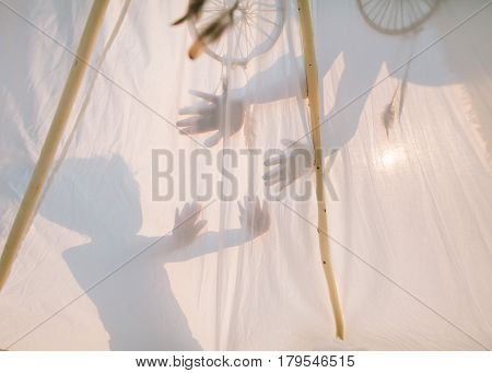 shadows of children's palms on a white tent in sunny day. a concept of a game of children outdoor.