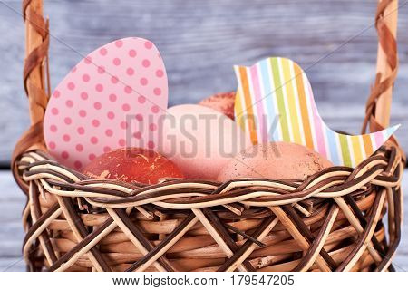 Eggs and colorful paper cutouts. Easter basket close up.