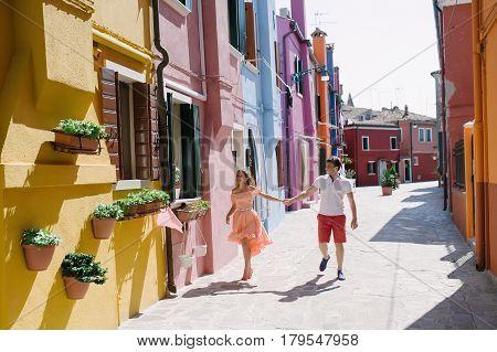 Beautiful couple walking holding hands in Burano island Venice Italy