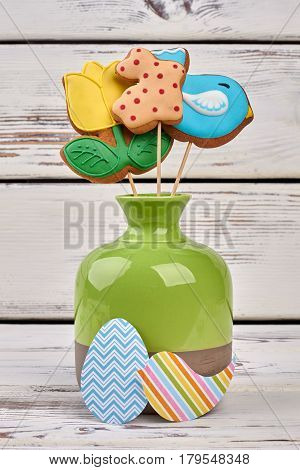 Easter cookies and paper crafts. Vase with biscuits on wood.