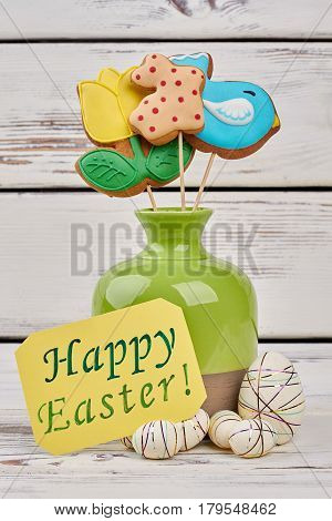 Easter greeting card and cookies. Polystyrene eggs on wood.