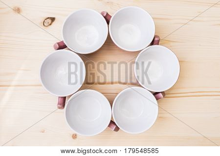 6 empty tea mugs standing in a circle on a wooden table