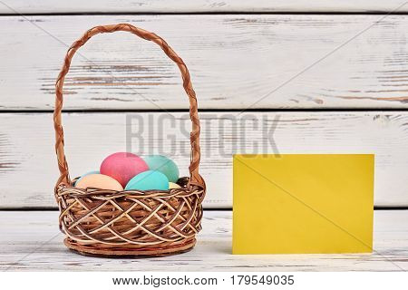 Easter basket and blank card. Empty yellow paper on wood.