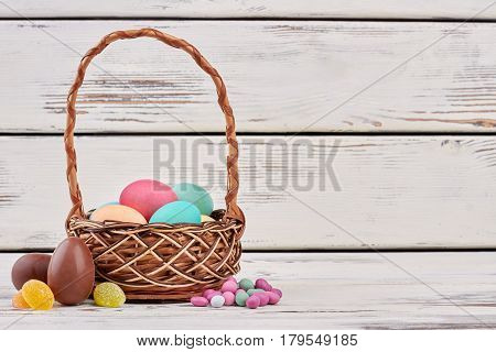 Candies and Easter egg basket. Sweets on wooden surface. Easter goodies ideas.