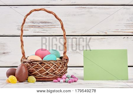 Easter basket and blank paper. Sweets on white wood.