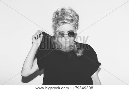 Stylish fashion sexy blonde bad girl in a black t-shirt and rock sunglasses. Dangerous rocky emotional woman. Black and white toned. White background, not isolated