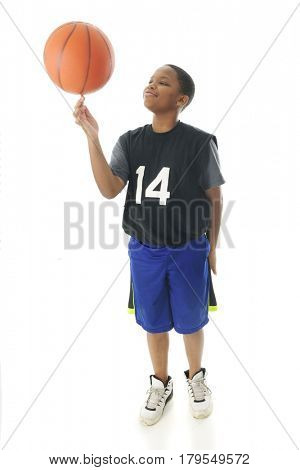 A handsome preteen boy proudly spinning his basketball on his index finger.  Motion blur on the ball.  On a white background.