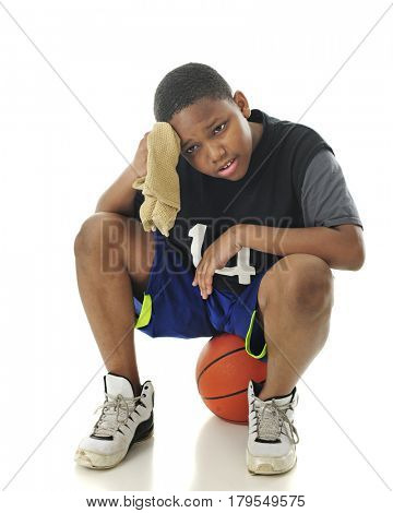 A preteen athlete looking tired and wiping his brow while resting on his basketball.  On a white background.