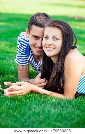 Photo Of Cute Couple Smiling And Lying On The Grass In The Field