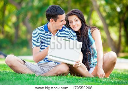 Photo Of Cute Couple Sitting With The Laptop And Smiling On The Trees Background