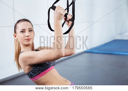 Photo of beautiful young sporty woman. Woman training with TRX Suspension at fitness club. Woman looking at camera