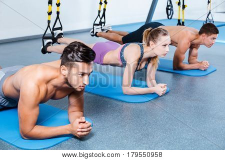 Photo of handsome men and beautiful woman. Sporty people training with TRX Suspension at fitness club