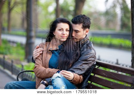Photo Of Cute Couple Sitting On The Bench And Hugging On The Wonderful Park Background