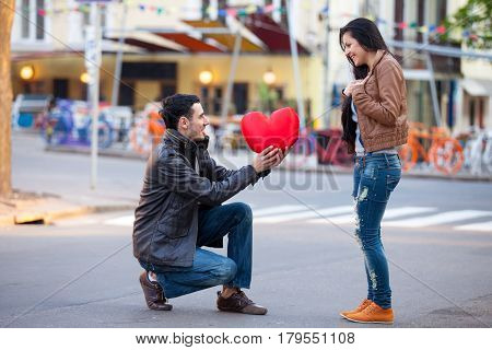 Photo Of Cute Couple With Heart Shaped Toy On The Wonderful Street Background