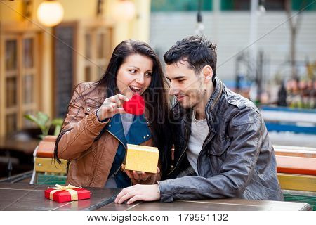 Photo Of Cute Couple Sitting On The Bench And Looking At The Heart Shaped Toy On The Wonderful Cafe
