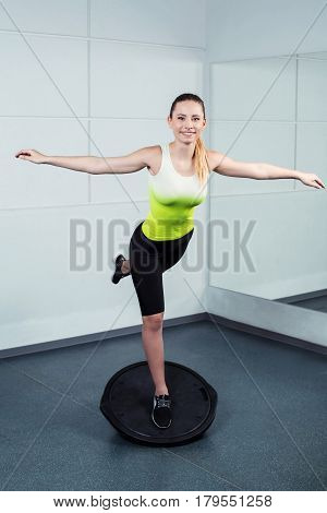 Photo of beautiful young sporty woman. Fitness girl working out with bosu at fitness club. Woman smiling and looking at camera
