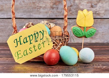 Greeting card and dyed eggs. Basket on brown wood. Have a happy Easter.