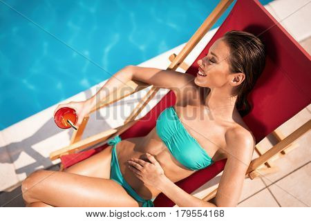 Beautiful woman enjoying summer and tanning at pool