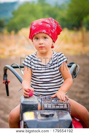 Child In Red Bandana And Stripe Tee  Sits On Tiller On The Field. Baby Girl Driver Cultivator