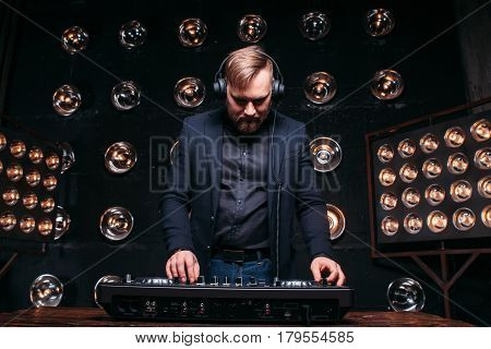 Charismatic DJ in headphones at the console checking equipment. Disk jockey plays on the best, famous CD players at nightclub during party, music festival.