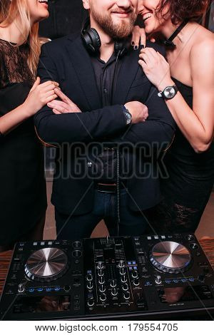 Two unrecognizable laughing attractive sexy girls with disk jockey at nightclub party. Communication, flirt, relax, nightlife clubbing, lifestyle, leisure.