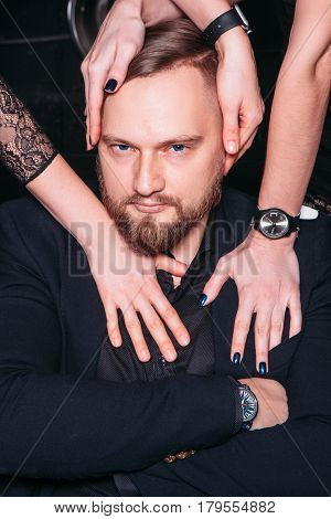 Portrait of young blue eyed handsome bearded macho man wanted by women passionately. Unrecognizable women's hands touching his head and shoulders with desire.