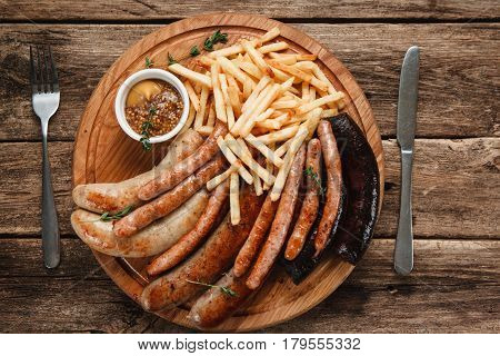 Oktoberfest traditional menu, German food. Grilled hot sausages with tasty sauce and french fries, top view.