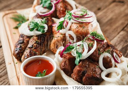 Assorted delicious grilled meat served on pita bread with herbs, onion, and tomato sauce, close up view. Restaurant menu photo.
