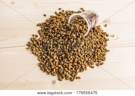 Dry pet nutrition with a measuring cup on a wood background top view.Health pet concept