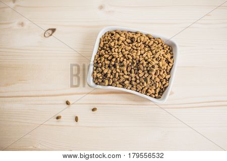 Dry pet nutrition In the bowl And a little scattered near on a wood table.Health pet concept