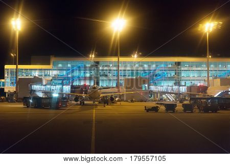 Passenger Plane And Busses At Night Airport.