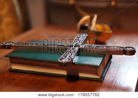 The prayer book, the orthodox cross and the box with the chrism during the Baptismal ceremony