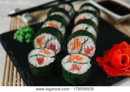 Delicious and appetizing set of sushi served on black slate on Japanese restaurant, closeup. Fresh yin yang maki, Asian cuisine, healthy food art.