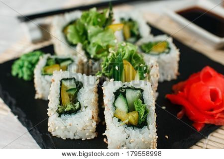 Appetizing and yummy sushi uramaki rolls with avocado, cucumber and lettuce, served on black slate with ginger and wasabi. Japanese delicacy for gourmet.