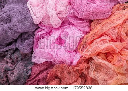 Multicolored background of purple lilac rose red orange and crimson colors of gauze fabric