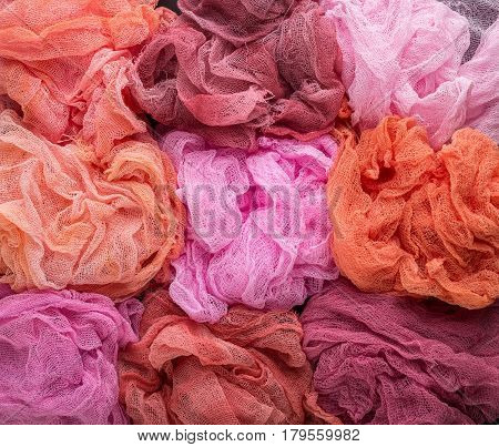 Multicolored background of pink red orange and crimson colors of gauze fabric
