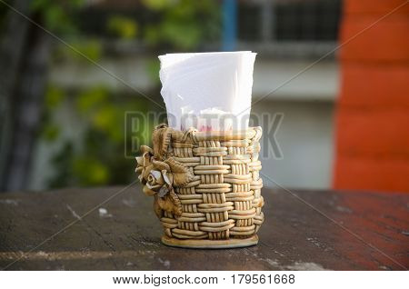 Rattan weave Box of tissues and toothpick on wooden table at hotel