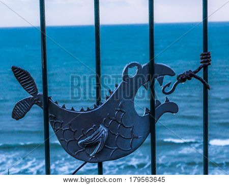 Metal Ornament On A Balustrade In A Seaside Village, Symbolic In The Shape Of A Fish