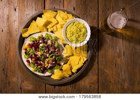 Mexican tortillas with meat red beans Jalapeno pepper nachos chips beer and salsa guacamole over an old wooden table