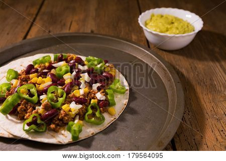 Mexican tortillas with meat red beans Jalapeno pepper and salsa guacamole over a platter