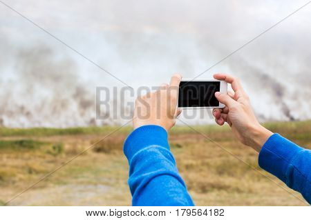 the person holding cellphone in hand and documenting the strongest summer fire and smoke among fields