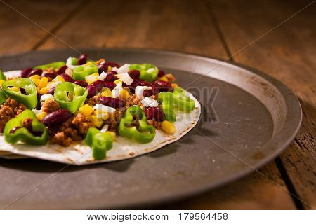 Mexican tortillas with meat red beans Jalapeno pepper and onion over a platter